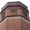 Detail of the Four Winds building chimney base showing the sandstone panels with the carved scuptures depicting the South and East Winds.
